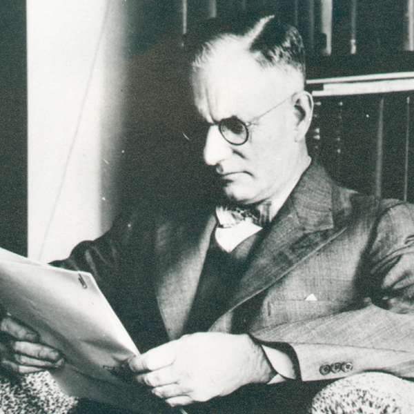 John Curtin sitting and reading documents